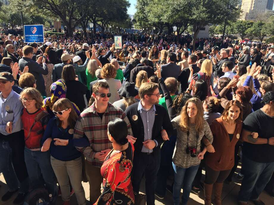 Hundreds of people lock arms outside the Texas state Capitol to create a human shield several rows deep around speakers at the Texas Muslim Capitol Day rally on Tuesday, Jan. 31, 2017.