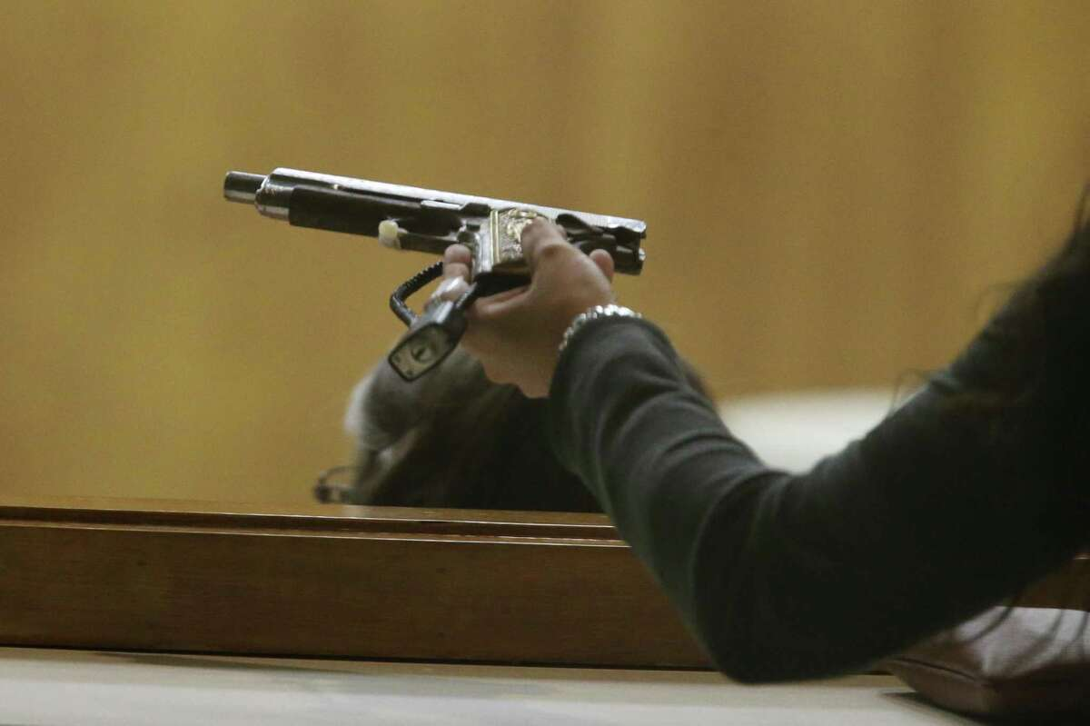Members of the jury handle a handgun introduced as evidence in the capital murder trial of U.S. Border Patrol Agent Joel Luna, and his brother, Eduardo Luna, 27, in Brownsville, Texas, Wednesday, Jan. 18, 2017. They and their elder brother, Fernando Luna, 37, were charged in the murder of Honduran immigrant Jose Francisco Rodriguez Palacios Paz, 33. The Honduran was found decapitated off South Padre Island in March of 2015. Also charged in the death are Aaron Rodriguez Medellin, 22 and Nestor Manuel Leal, 18. The elder Lune pled a deal in exchanged for testifying against his brothers.