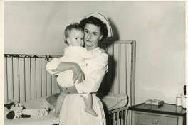 Working in the pediatrics ward is Mrs. George Smith's favorite, and no wonder, as this young tyke shows her implicit trust in the protective arms of the nurse. May 2, 1953