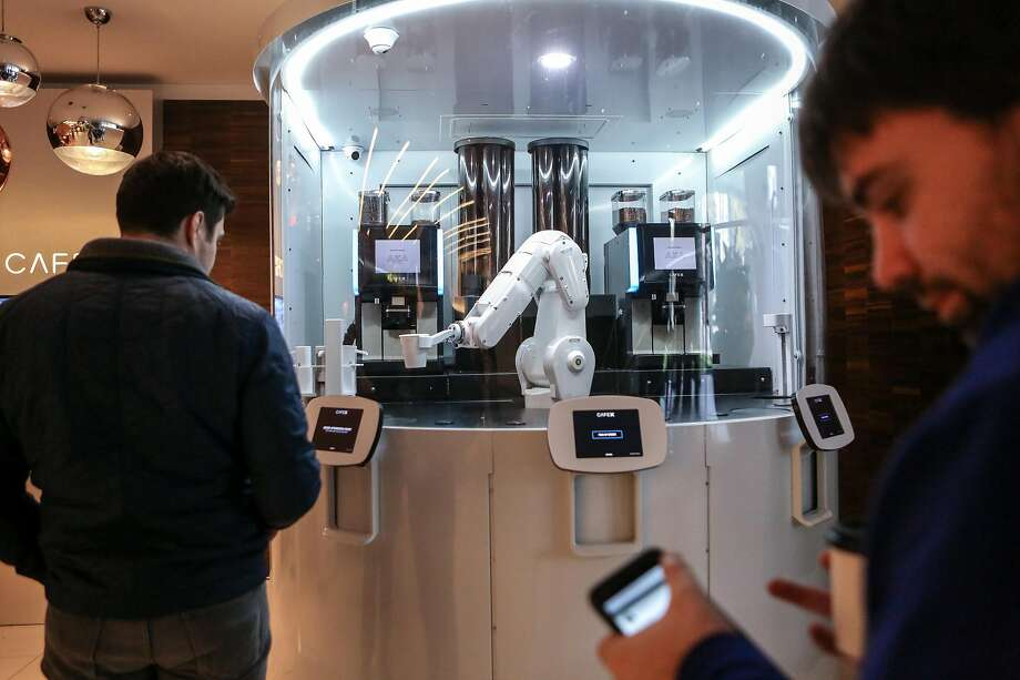 Customers try out the new robotic cafe, Cafe X, in the Metreon in San Francisco. A robot arm will prepare your latte. Photo: Amy Osborne, Special To The Chronicle