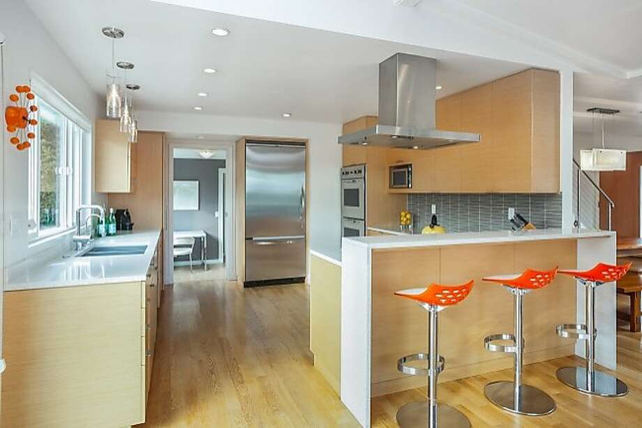 The remodeled kitchen at 239 McNear Drive in San Rafael has dual ovens and a breakfast bar counter with waterfall edges.