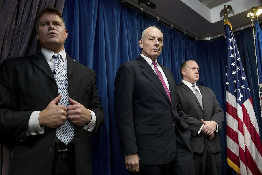 Homeland Security Secretary John Kelly, center, accompanied by U.S. Immigration and Customs Enforcement Acting Director Thomas Homan, right, and a member of his security detail, attends a news conference at the U.S. Customs and Border Protection headquarters in Washington, Tuesday, Jan. 31, 2017, to discuss the operational implementation of the president's executive orders. (AP Photo/Andrew Harnik) Photo: Andrew Harnik, Associated Press