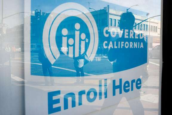 Pedestrians are seen reflected in a sign for Covered California at the Asian Health Services offices on the final day of open enrollment for Covered California, the state's health insurance marketplace created by the Affordable Care Act, in Oakland, CA on Tuesday, January 31, 2017.