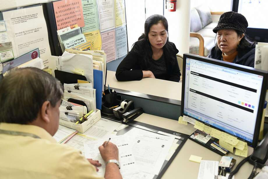 Customers Minh Nguyen, center, and her mother Mui Vong get help form member services representative Wayee Thieu at the Asian Health Services offices on the final day of open enrollment for Covered California, the state's health insurance marketplace created by the Affordable Care Act, in Oakland. Photo: Michael Short, Special To The Chronicle