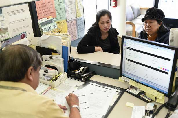 Customers Minh Nguyen, center, and her mother Mui Vong get help form Member services representative Wayee Thieu at the Asian Health Services offices on the final day of open enrollment for Covered California, the state's health insurance marketplace created by the Affordable Care Act, in Oakland, CA on Tuesday, January 31, 2017.