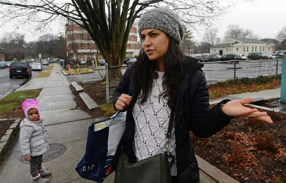 Library patron Saghar Lavine with her daughter, Mitra Lavine, 2, complains about the lack of parking for the Norwalk Public Library Main Branch on Belden Avenue Tuesday, January 17, 2017,  in Norwalk, Conn. There is an ongoing appeal of the Norwalk Zoning Commission's 2016 approval of a 60-unit apartment complex for the Mott Avenue lot that had been available for library visitors. Photo: Erik Trautmann / Hearst Connecticut Media / Norwalk Hour