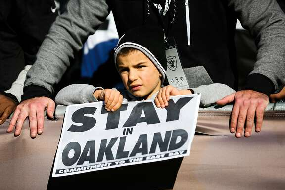 """Raiders fan Kryiakos Konstantine, 6, holds up a sign saying """" Stay in Oakland"""" during a game between the Oakland Raiders and the Indiana Colts, in Oakland, Calif., on Saturday, Dec. 24, 2016."""