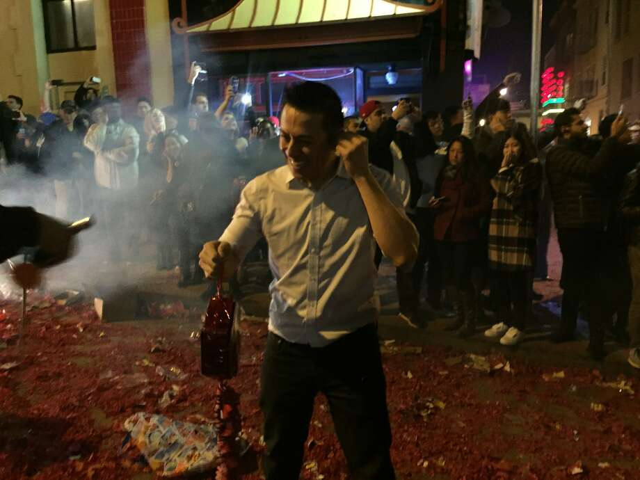 Jerry Chan, owner of Red's Place in Chinatown, prepares to light a strand of 100,000 firecrackers at the stroke of midnight on the eve of the Chinese New Year. Photo: Beth Spotswood
