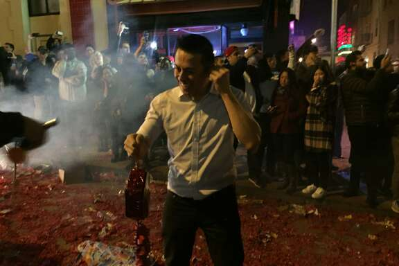 Jerry Chan, owner of Red's Place in Chinatown, prepares to light a strand of 100,000 firecrackers at the stroke of midnight on the eve of the Chinese New Year.