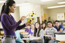 Teacher explaining chemistry model to classroom