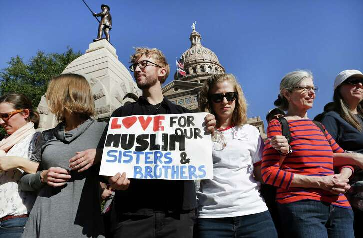 Jonathan Krugman, left, holds a sign with Whitney Thurman, right, next to him during the Texas Muslim Capitol Day, in Austin, Texas on Tuesday, Jan. 31, 2017.