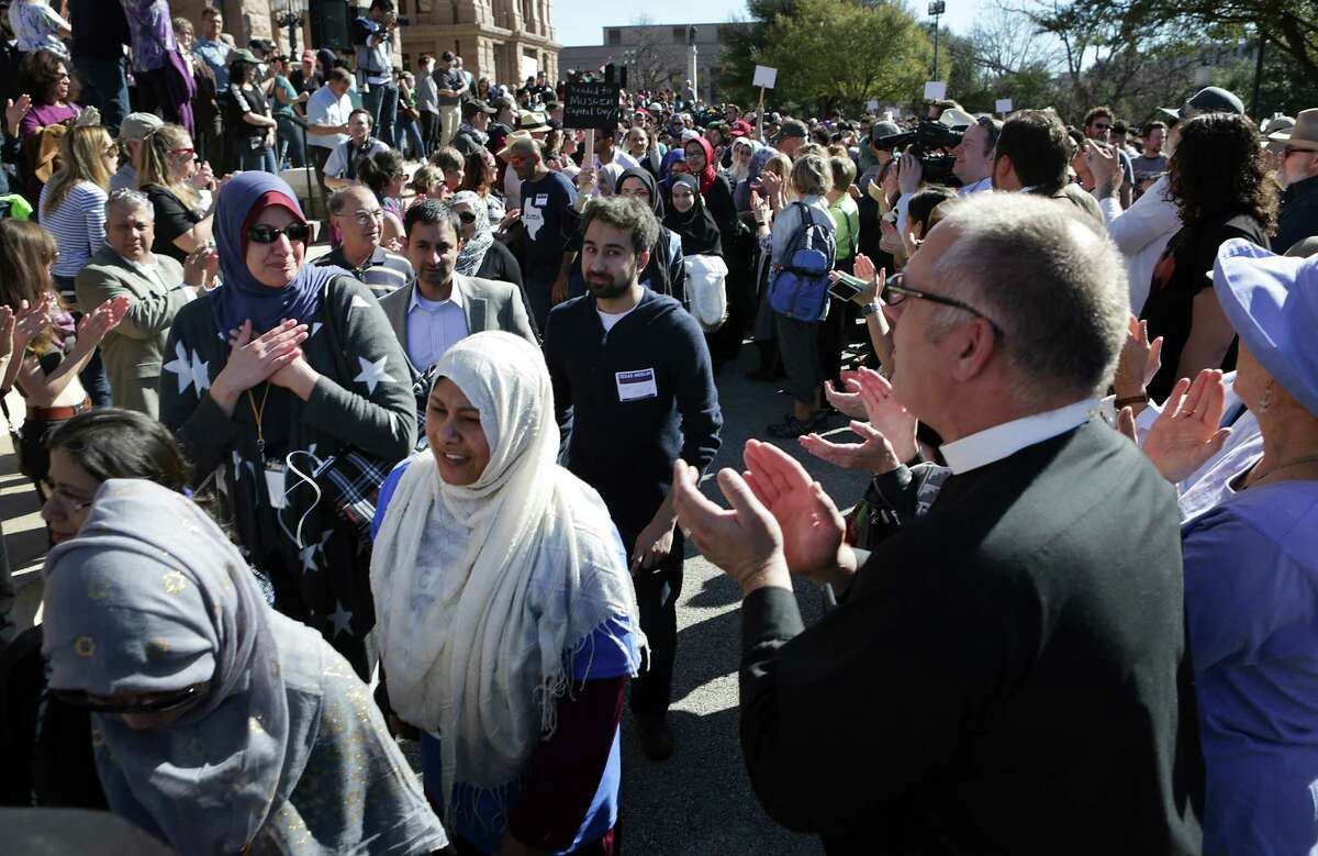 Pastor Brad Fuerst, right, of the Lutheran Campus Ministry at UT, and others applaud some of the 800 Muslims as they walk to the First United Methodist Church where the group held meetings following the Muslim Capitol Day, in Austin, Texas on Tuesday, Jan. 31, 2017.