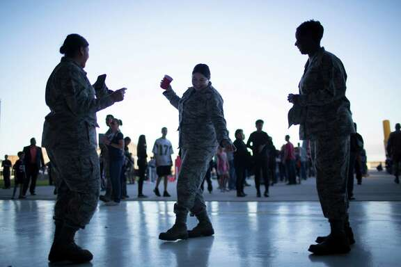 U.S. Air Force staff sergeant Sonia DeLeon, center, dances to country music with master sergeant Kimberly Crowford, right, and senior master sergeant Monica Jackson, left, during the Super Bowl LI salute to service barbecue at the Ellington Field Joint Base Reserve, Tuesday, Jan. 31, 2017, in Houston.