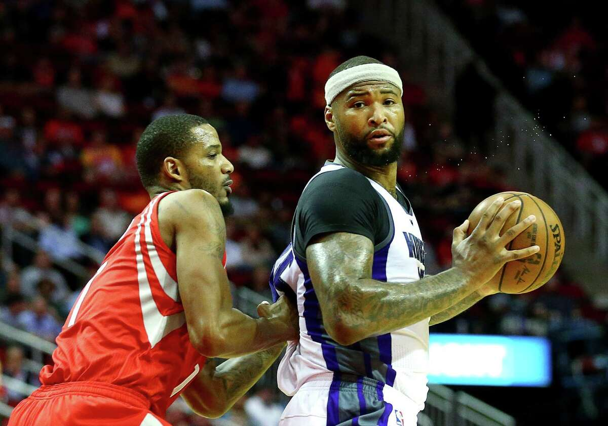 Sacramento Kings forward DeMarcus Cousins (15) looks to pass while defended by Houston Rockets forward Trevor Ariza (1) during the second quarter of an NBA game at the Toyota Center, Tuesday, Jan. 31, 2017, in Houston.