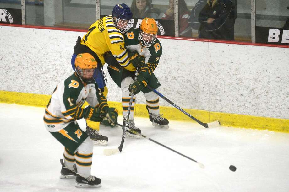 From left, Dow's Brendan Holbrook, Midland's Carson Kraenzlein and Dow's Nathan Painter fight for possession of the puck on Tuesday at the Midland Civic Arena. Photo: Erin Kirkland/Midland Daily News