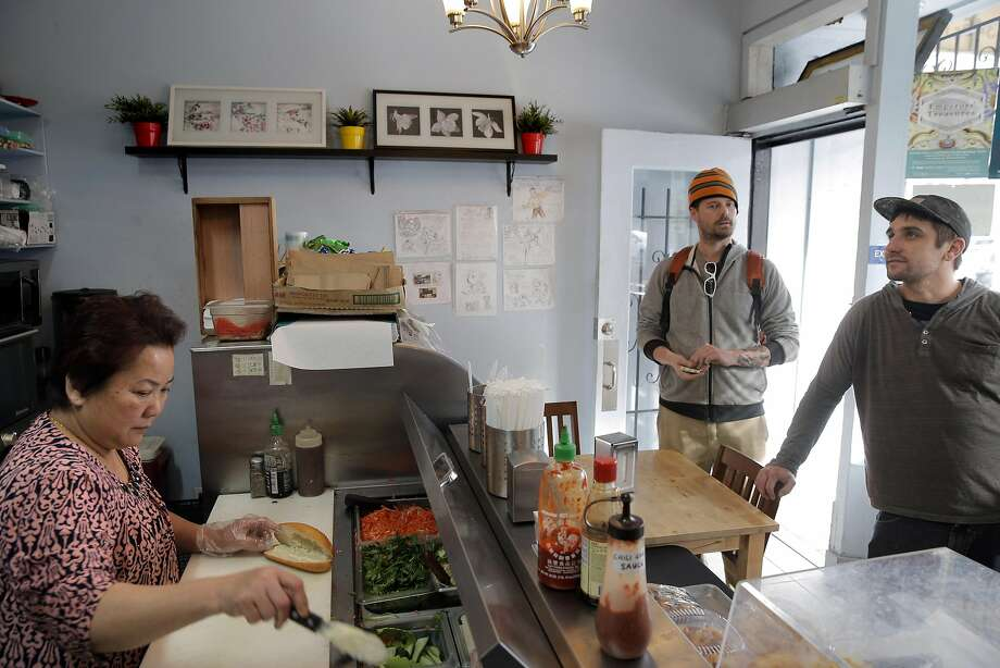 Ki Giang prepares a sandwich for Glenn Stigge, right, and Mark Hullander, center, at the L & G Vietnamese Sandwich shop after they made a pitstop after dropping a friend off at the airport in San Francisco, Calif., on Tuesday, January 31, 2017. Minh Lam and his wife Ki Giang opened the shop several years ago as their son, Aaron, began college while still helping out around the shop. Photo: Carlos Avila Gonzalez, The Chronicle