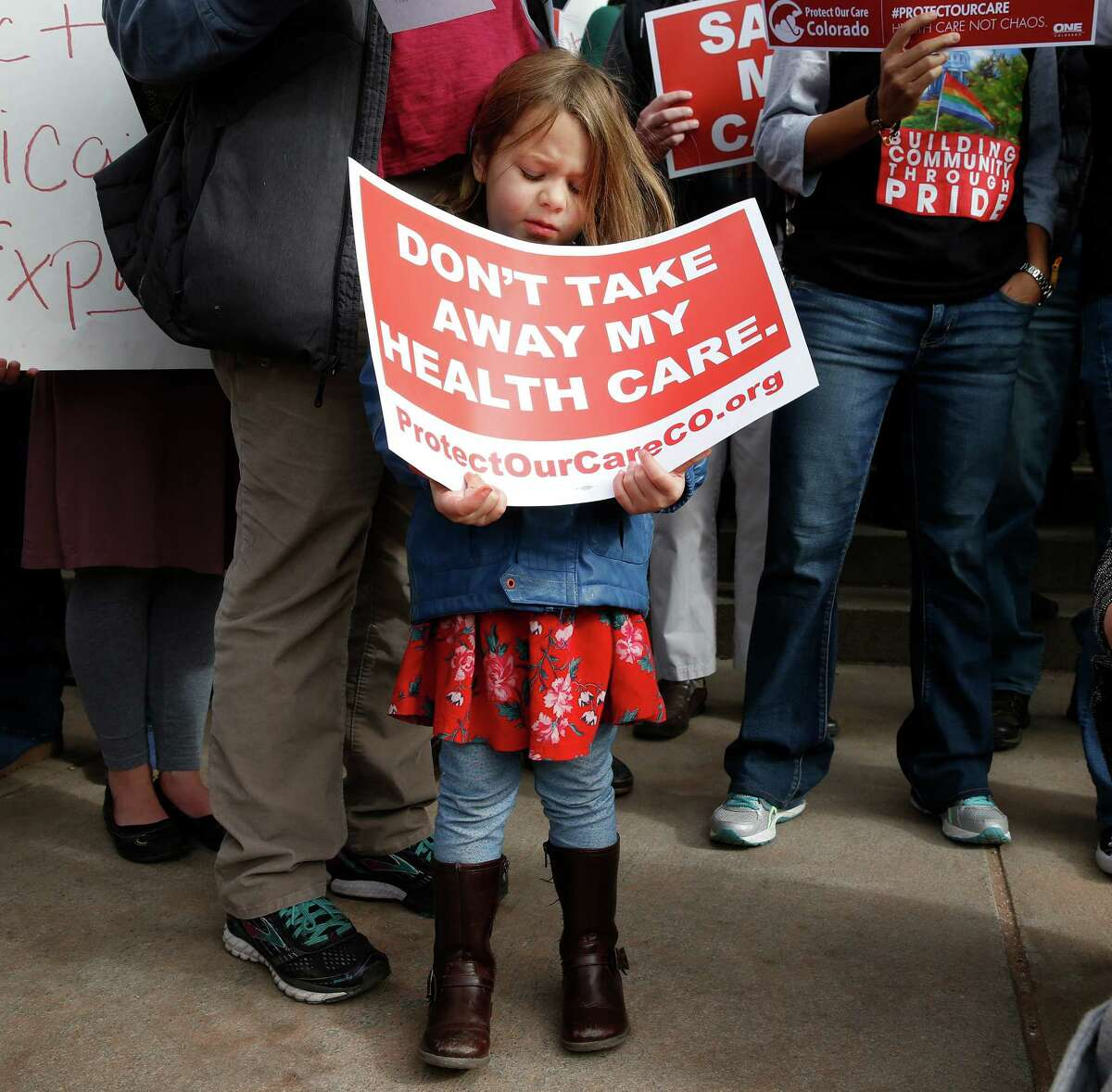 A girl stands holding a sign alongside supporters of the Affordable Care Act who are also opponents of Colorado's GOP-led plan to undo Colorado's state-run insurance exchange at a rally on the state Capitol steps in Denver, Tuesday, Jan. 31, 2017. The state GOP measure, a bill which would dismantle Connect For Health Colorado within a year, is an indication of how Republicans plan to chip away at Obamacare. If the federal health care law remains unchanged, it would force Coloradans shopping for private insurance to use the federal exchange. (AP Photo/Brennan Linsley)