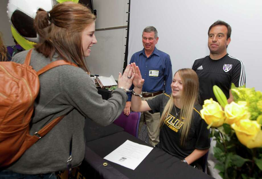 Destiny Haliburton gets a high-five after signing to play soccer for Texas Lutheran University during a National Signing Day ceremony at Willis High School Wednesday, Feb. 1, 2017, in Willis. Six Willis athletes signed National Letters of Intent to play collegiate athletics. Photo: Jason Fochtman, Staff Photographer / © 2017 Houston Chronicle