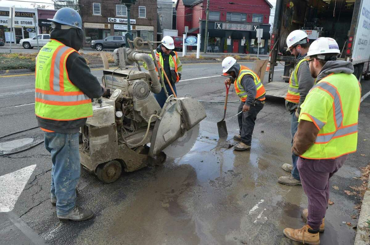 Workers use a saw to cut into the pavement along East Avenue. on Dec. 7. This work is necessary to perform subsurface investigations for existing utilities related to the construction required for the Walk Bridge Replacement Project in Norwalk.