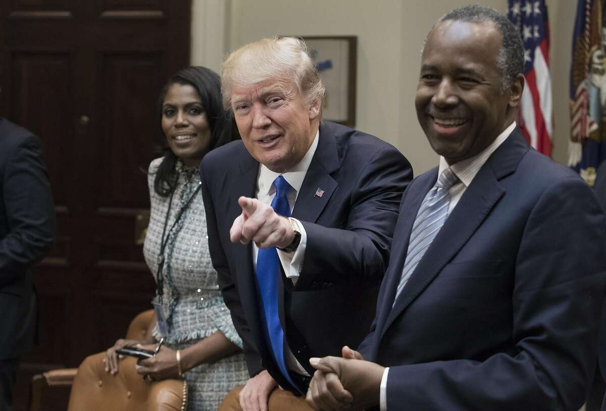 President Donald Trump holds an African American History Month listening session attended by nominee to lead the Department of Housing and Urban Development (HUD) Ben Carson (right), Director of Communications for the Office of Public Liaison Omarosa Manigault (left) and other officials in the Roosevelt Room of the White House on February 1, 2017 in Washington, DC.