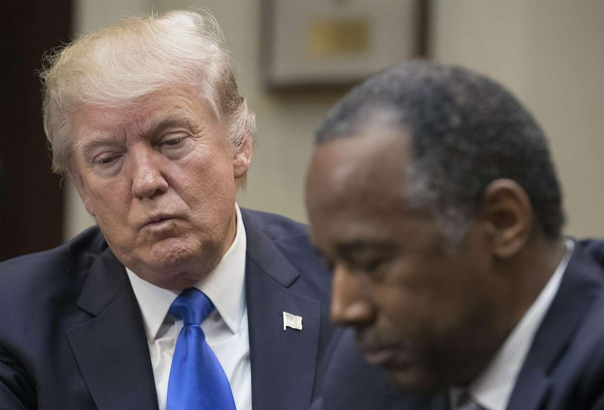 President Donald Trump holds an African American History Month listening session attended by nominee to lead the Department of Housing and Urban Development (HUD) Ben Carson (right) and other officials in the Roosevelt Room of the White House on February 1, 2017 in Washington, DC.