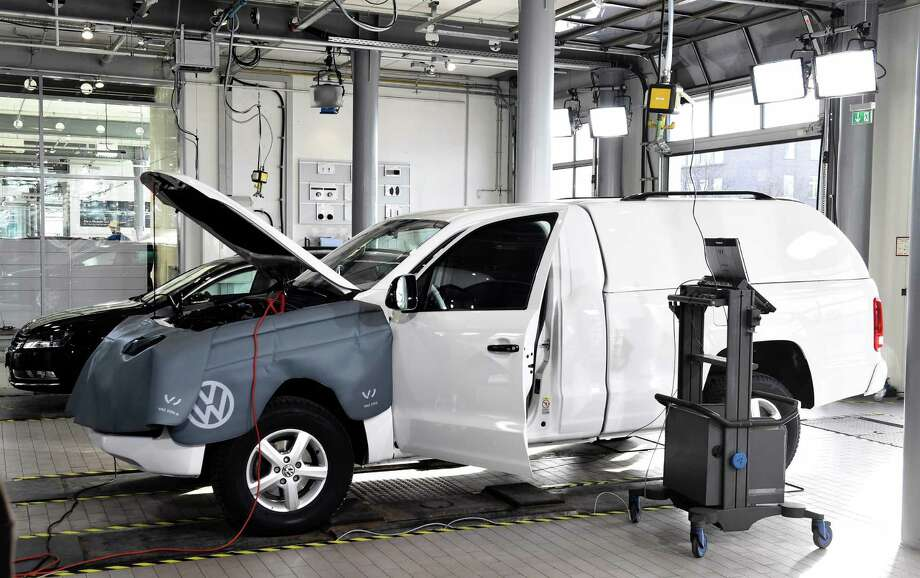 A Volkswagen Amarok car is linked to a computer during a software update. A federal judge in San Francisco granted initial approval Tuesday to a deal worth at least $1.2 billion that aims to compensate the owners of roughly 78,000 Volkswagens. Photo: AFP /Getty Images /File Photo / AFP or licensors