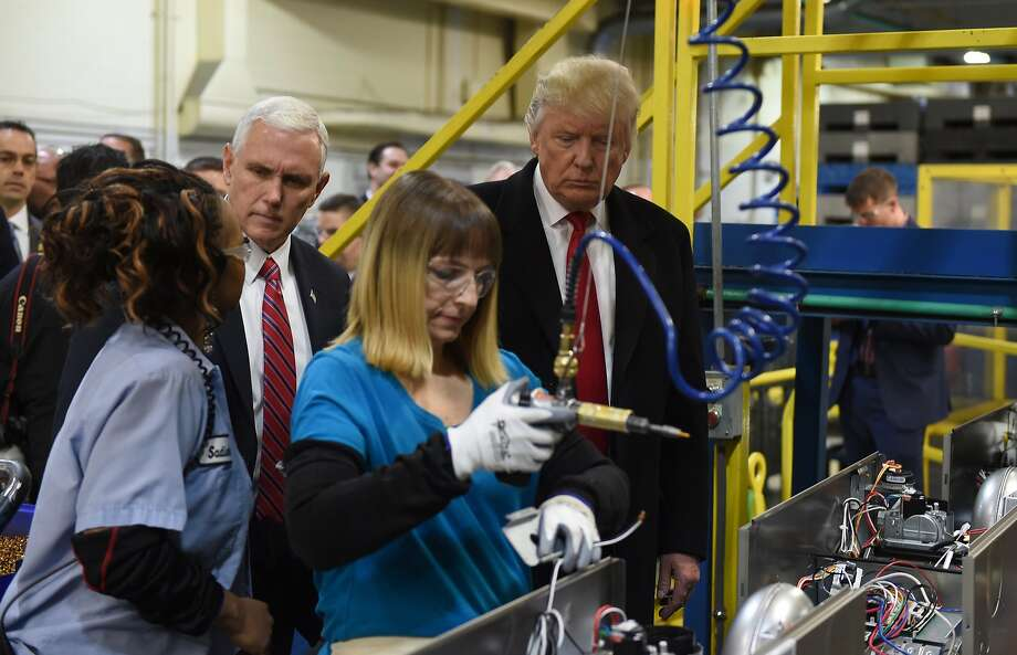 (FILES) This file photo taken on December 1, 2016 shows US President Donald Trump(R) and US Vice President-elect Governor Mike Pence during thier visit to the Carrier air conditioning and heating company in Indianapolis, Indiana. US manufacturing activity expanded in January for the fifth consecutive month as production, employment and prices all improved, and orders held steady, the Institute for Supply Management said on February 1, 2017. The ISM manufacturing index rose 1.5 points to 56 percent -- the highest since November 2014 -- with a strong majority of the industries surveyed reporting growth.  / AFP PHOTO / TIMOTHY A. CLARYTIMOTHY A. CLARY/AFP/Getty Images Photo: TIMOTHY A. CLARY, AFP/Getty Images