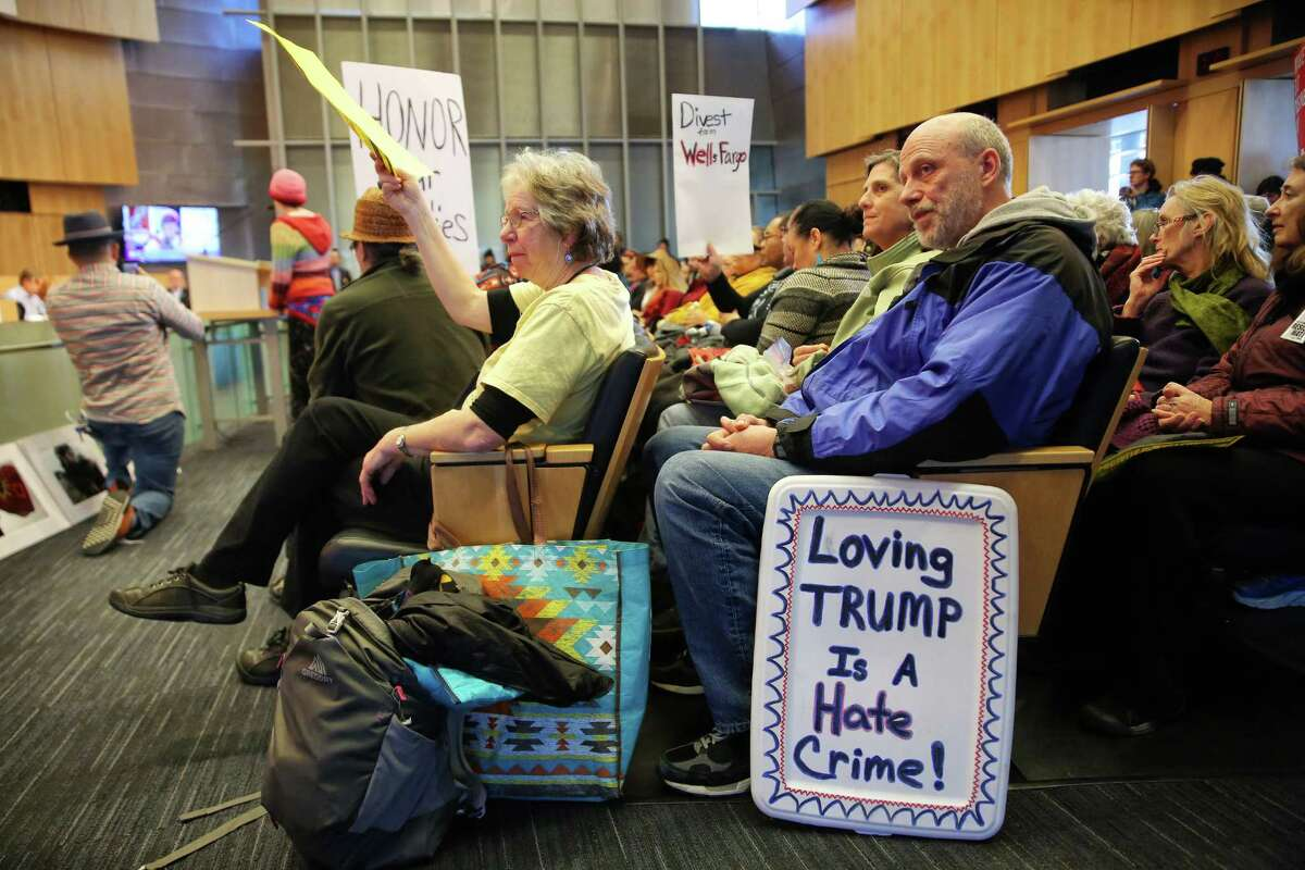 People hold signs in the chambers of Seattle City Hall, Wednesday morning, as the City Council holds a Finance Committee meeting on divesting about $3 billion in city money from Wells Fargo Bank because of the bank's involvement in the Dakota Access Pipeline.