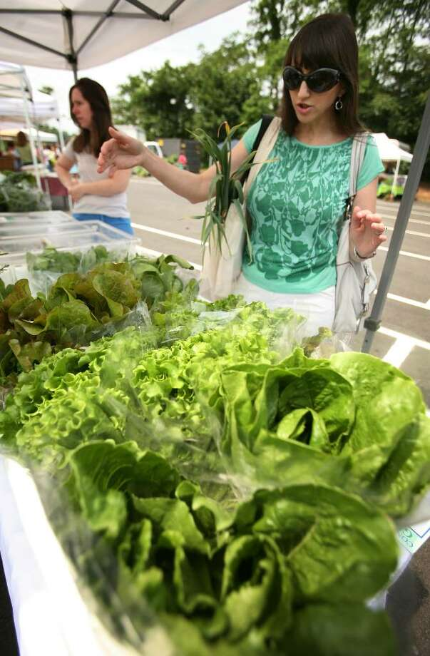 Analiese Paik, right, founder of the Fairfield Green Food Guide, shops for fresh locally grown produce at the Westport Farmers Market recently. Photo: Brian A. Pounds / Connecticut Post