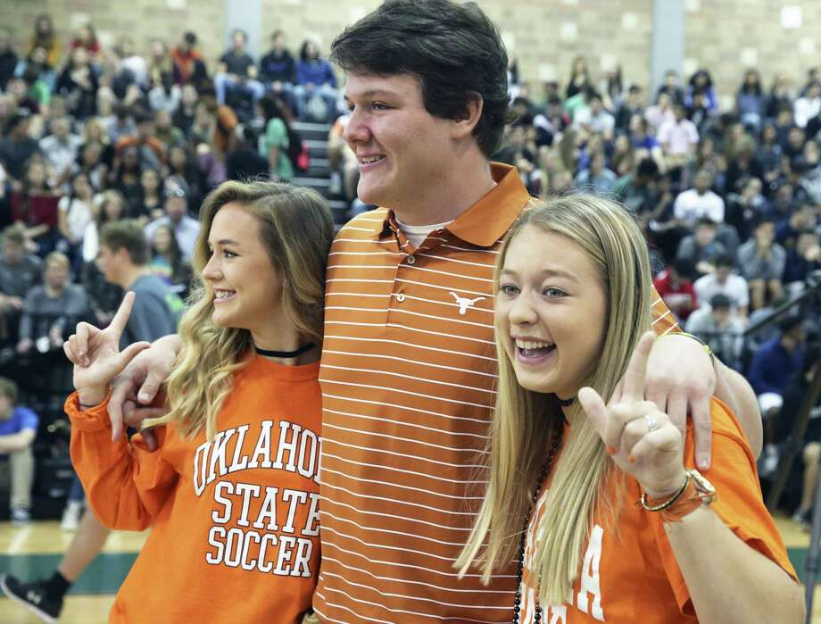 Oklahoma State soccer signees Lauren Anderson (left) and Taylor Olson have some fun posing for photos with UT football signee Derrick Kerstetter as Reagan High School athletes sign scholarship papers on national signing day, February 1, 2017. Photo: Tom Reel, Staff / San Antonio Express-News / 2017 SAN ANTONIO EXPRESS-NEWS