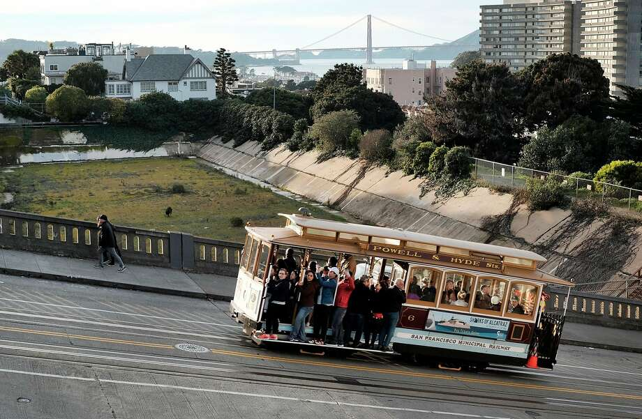 A cable car makes it's way up Hyde St. next to the empty Francisco Reservoir in the Russian Hill neighborhood of San Francisco, CA on Sunday, January 29, 2017. Photo: Michael Short, Special To The Chronicle