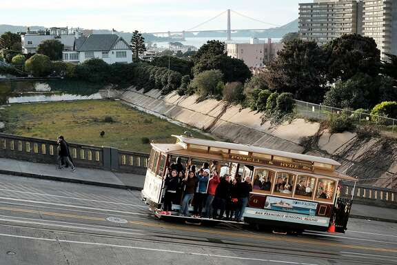 A cable car makes it's way up Hyde St. next to the empty Francisco Reservoir in the Russian Hill neighborhood of San Francisco, CA on Sunday, January 29, 2017.