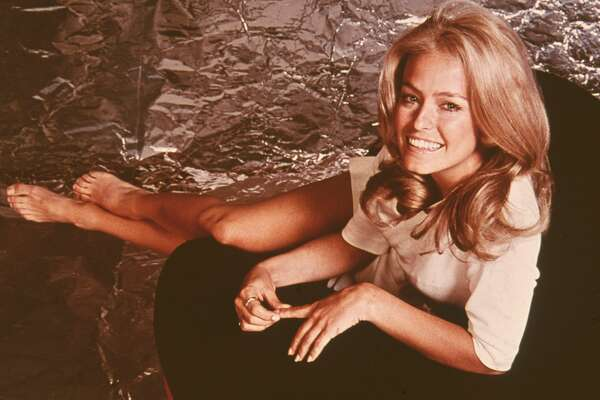 Portrait of American actress Farrah Fawcett dressed in a shirt as she sits and stretched her bare legs, early 1970s. (Photo by Fotos International/Getty Images)
