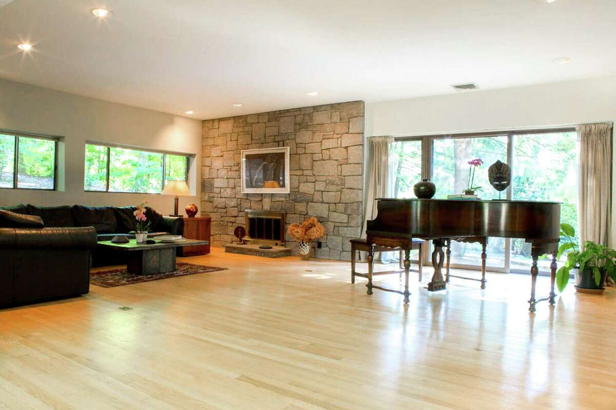 The living room has a floor-to-ceiling stone fireplace, one of three in the house.