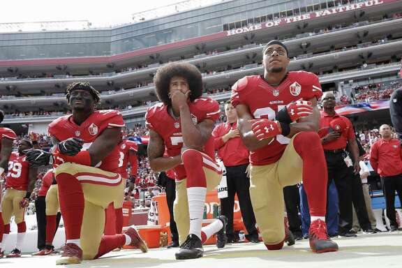 "In this Oct. 2 file photo, San Francisco 49ers quarterback Colin Kaepernick, center, kneels with teammates during the national anthem before an NFL football game against the Dallas Cowboys in Santa Clara, Calif. The Sacramento Bee reported that public opinion polls indicated that his taking a knee during ""The Star-Spangled Banner"" in support of Black Lives Matter may have played a part in the 11 percent drop in NFL viewership last year."