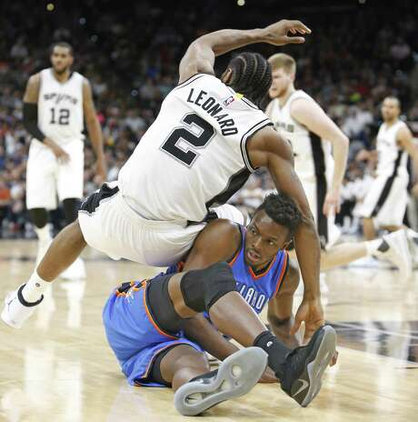 Kawhi Leonard og yhr Spurs falls over Anthony Morrow of the Oklahoma City Thunder at yjr AT&T Center on Jan. 31, 2017 in San Antonio. Photo: Ronald Cortes /Getty Images / 2017 Getty Images