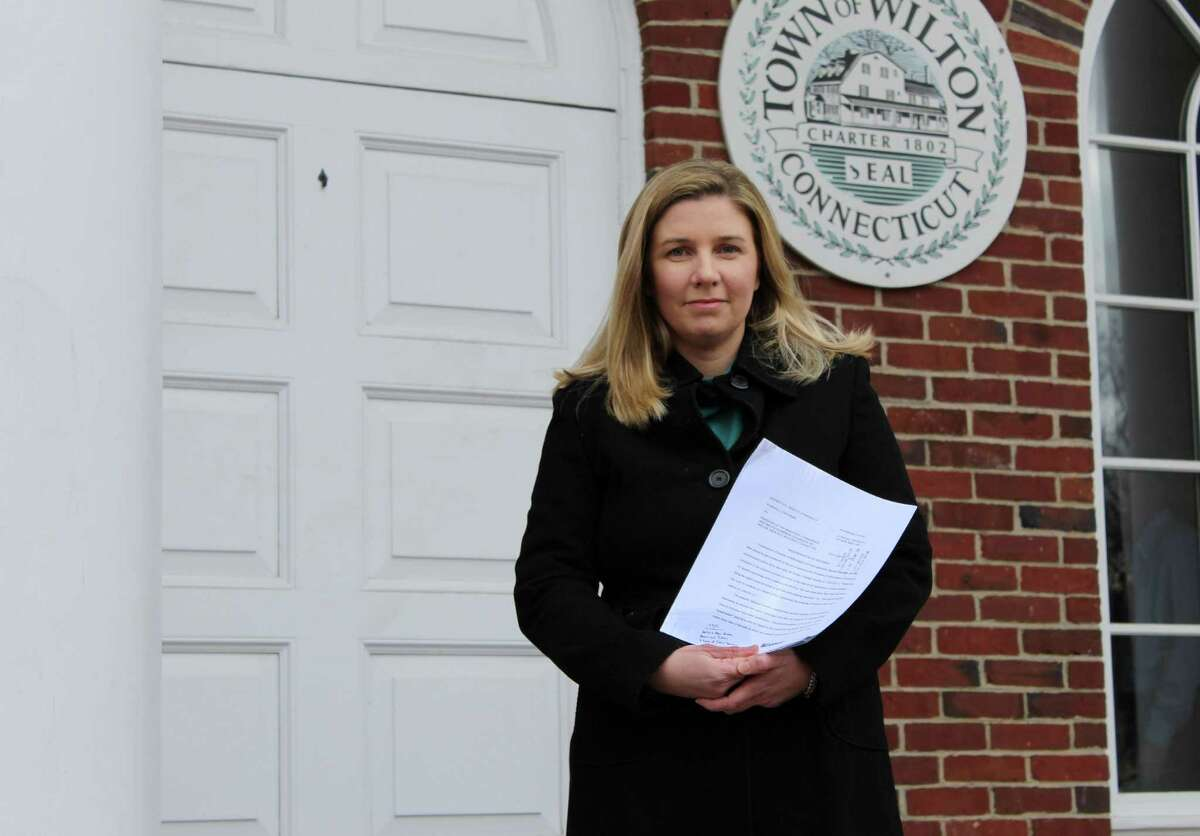 Marissa Lowthert holding the Superior Court's ruling in the lawsuit she filed against the Freedom of Information Commission in 2015.