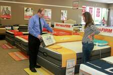 """Ben Wilson, area manager for Mattress Firm, helps customer Lisa Ellingsen at a Mattress Firm. Mattress Firm CEO Ken Murphy said in a statement the company is planning to """"revitalize"""" its stores this year with new products from manufacturers including Serta Simmons."""
