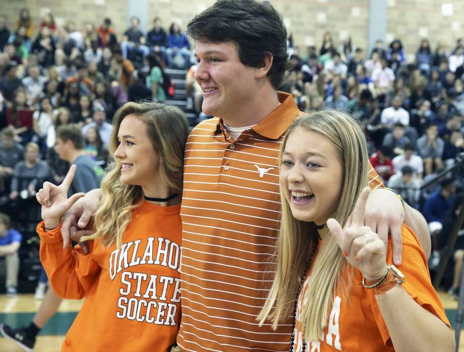 Oklahoma State soccer signees Lauren Anderson (left) and Taylor Olson have some fun posing for photos with UT football signee Derrick Kerstetter as Reagan High School athletes sign scholarship papers on national signing day, February 1, 2017. Photo: Tom Reel/San Antonio Express-News