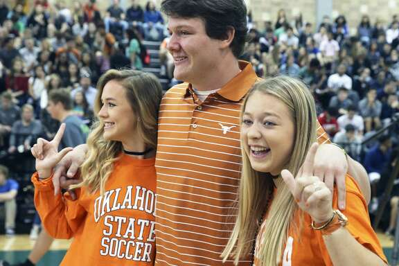 Oklahoma State soccer signees Lauren Anderson (left) and Taylor Olson have some fun posing for photos with UT football signee Derrick Kerstetter as Reagan High School athletes sign scholarship papers on national signing day, February 1, 2017.