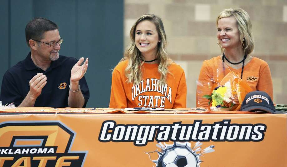 Lauren Anderson, surrounded by parents Darin and Jennifer, grins while being introduced as Reagan High School athletes sign scholarship papers on national signing day, February 1, 2017. Anderson will play soccer at Oklahoma State. Photo: Tom Reel/San Antonio Express-News
