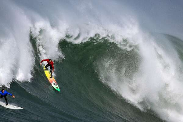 Ken Collins (red) and Chris Bertish (blue) try to get on a wave in heat number two in the first round of the Titans of Mavericks competition in Half Moon Bay , Calif., on Friday, February 12, 2016.