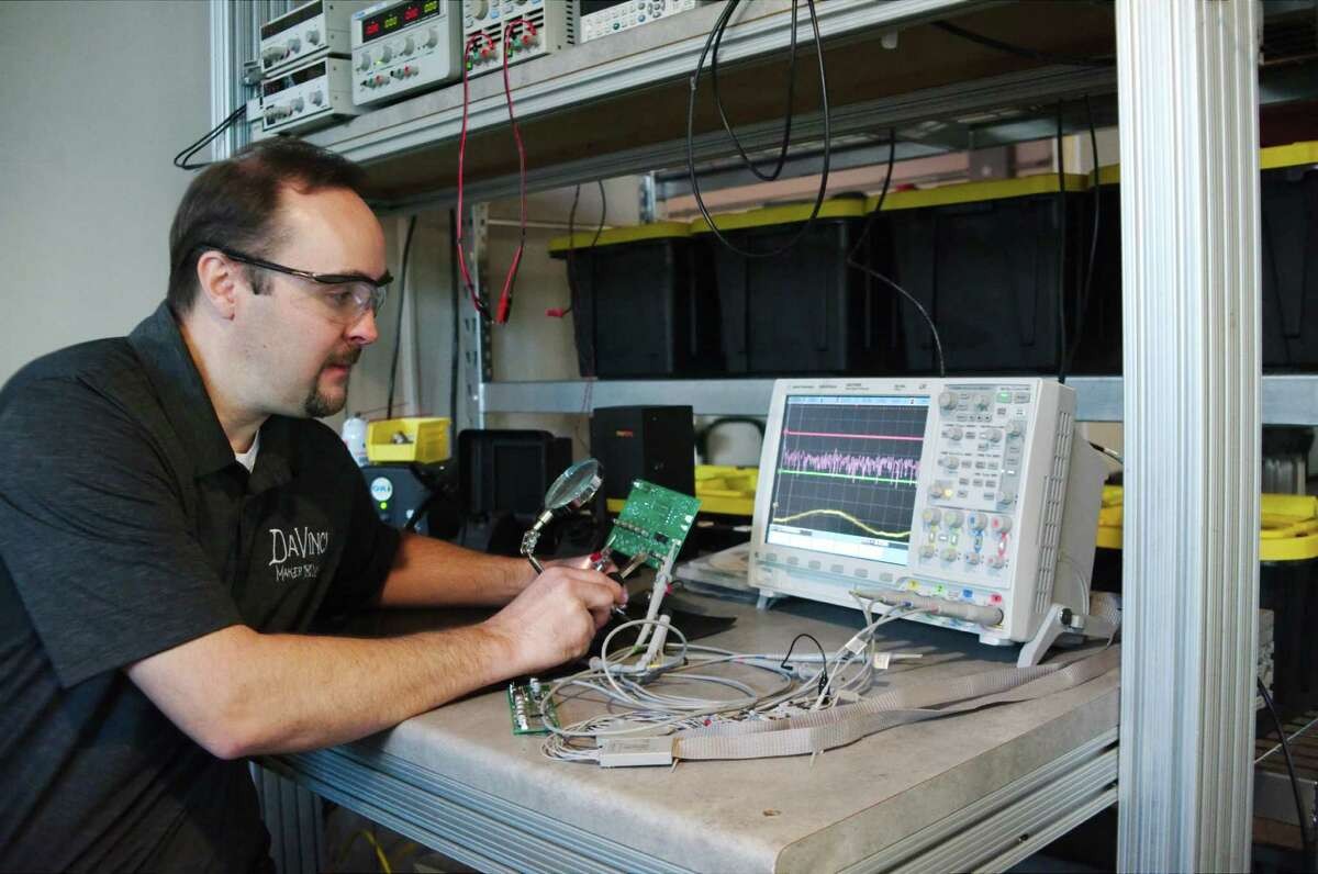 Davinci Maker Labs president Christopher Harris uses an oscilloscope to troubleshoot a circuit at the electronics station in his creative makerspace in Alvin.