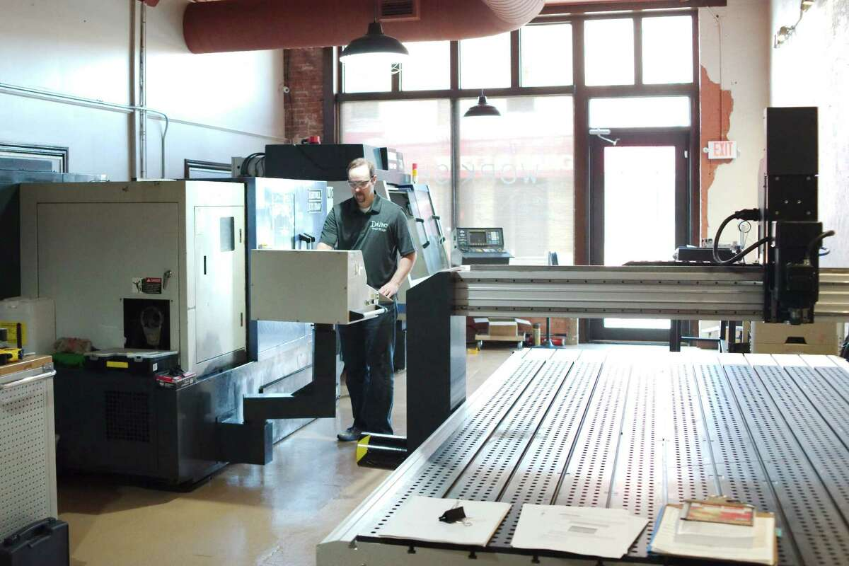 Davinci Maker Labs president Christopher Harris stands at the console of the CNC Lathe in the machine shop part of his creative makerspace in Alvin.