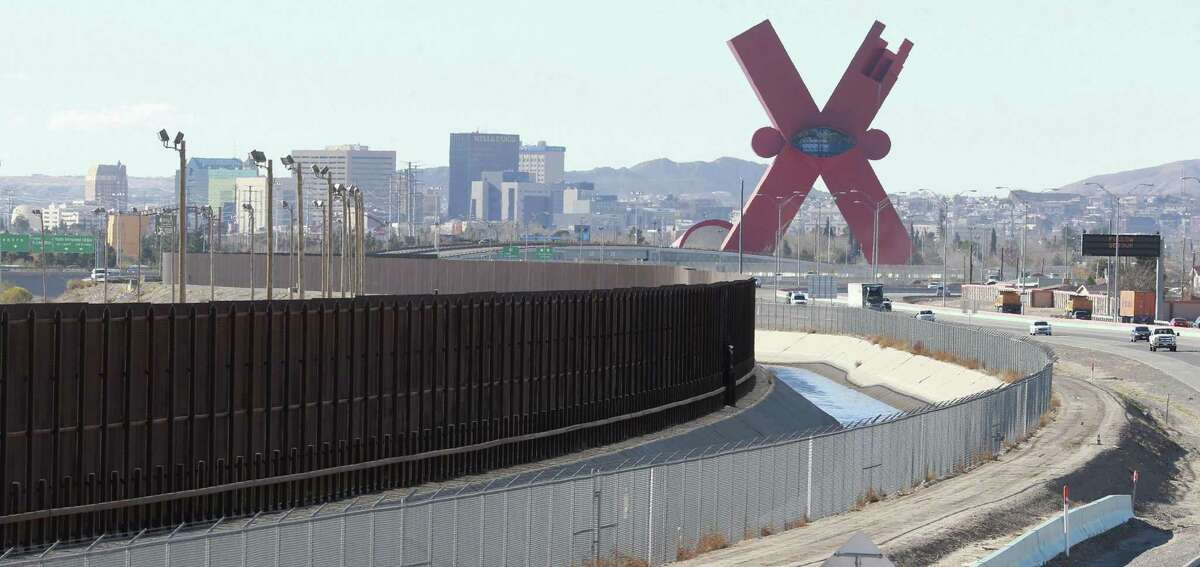"""Traffic moves on the El Paso border highway, right, next to the border fence which separates the U.S. and Mexico Wednesday Jan. 25, 2017 in El Paso, Texas. The El Paso skyline is in the background. The """"X"""" at right is in Juarez. The fence follows the path of the Rio Grande, not visible, which forms the border. A canal, which is on the U.S. side of the border is at right. (Victor Calzada/The El Paso Times via AP)"""