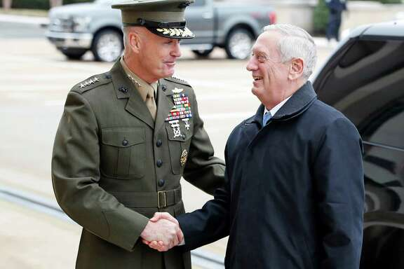 FILE - In this Jan. 21, 2107 file photo, Joint Chiefs Chairman Gen. Joseph Dunford greets Defense Secretary Jimn Mattis at the Pentagon. By visiting Japan and South Korea on his first official overseas trip, Mattis is seeking to reinforce key alliances after President Donald Trump's campaign-trail complaints that defense treaties disadvantaged the United States.(AP Photo/Alex Brandon, File)