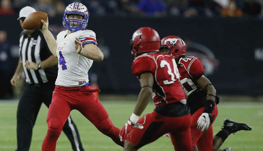 Austin Westlake quarterback Sam Ehlinger (4) rolls out looking for a receiver as Galena Park North Shore's Leandre Dever (34) and Noah Campbell (40) apply pressure during the Class 6A Division I state championship game in Houston on Dec. 19, 2015. Photo: Bob Levey /Associated Press / FR156786 AP