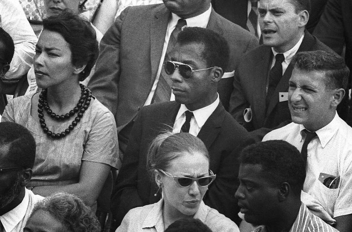 """This image released by Magnolia Pictures shows James Baldwin, center, in """"I Am Not Your Negro."""" In Raoul Peck's Oscar-nominated documentary, Baldwin's searing observations on race and America are resurrected for today. Peck and others say Baldwin's words could hardly be more urgent. (Dan Budnik/Magnolia Pictures via AP)"""