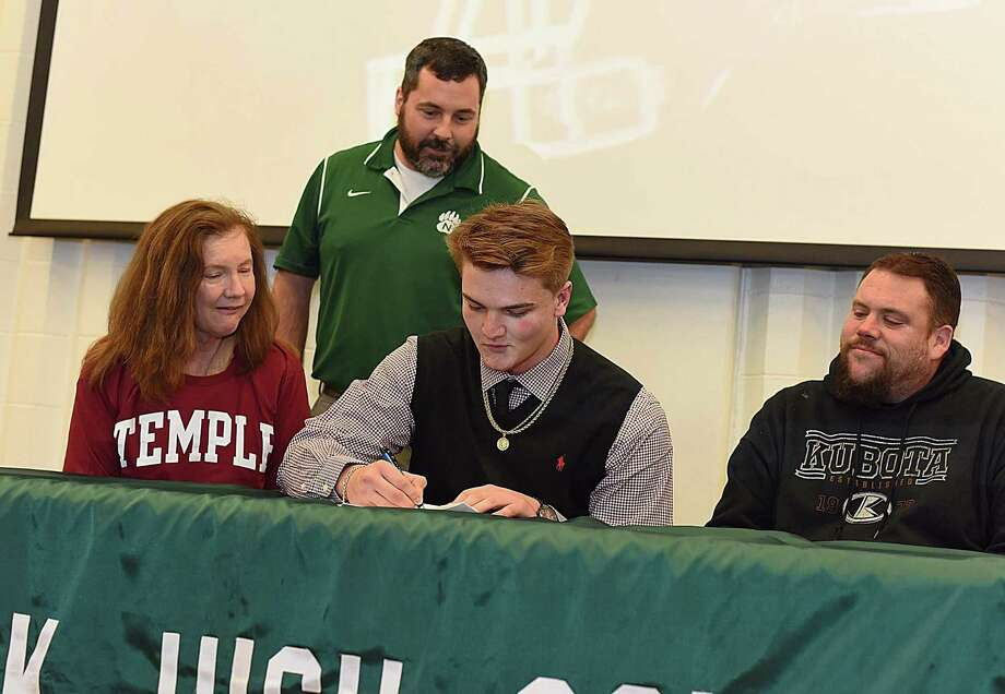 Norwalk High football player James Makszin, front and center, signs his National Letter of Intent to play football at Division 1 Temple University during a brief signing ceremony at the school on Wednesday. Makszin is flanked by his mother, left, and uncle as Bears football coach Sean Ireland oversees the signing. Photo: John Nash / Hearst Connecticut Media / Norwalk Hour