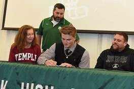 Norwalk High football player James Makszin, front and center, signs his National Letter of Intent to play football at Division 1 Temple University during a brief signing ceremony at the school on Wednesday. Makszin is flanked by his mother, left, and uncle as Bears football coach Sean Ireland oversees the signing.